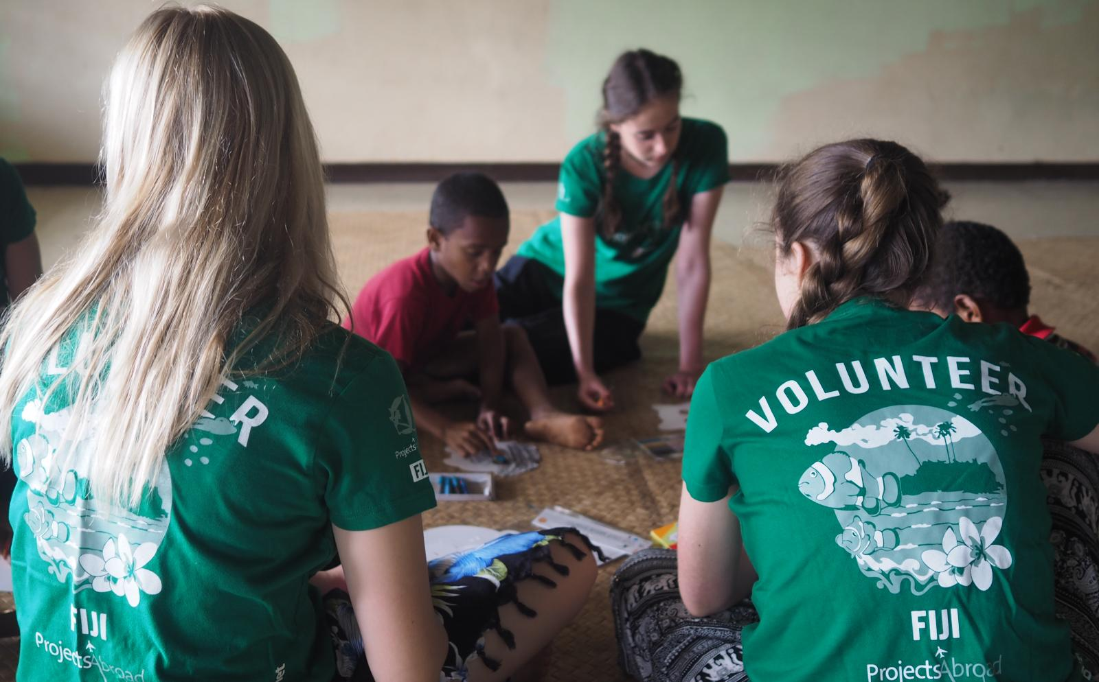 A Projects Abroad volunteer assists children in Fiji with their homework.